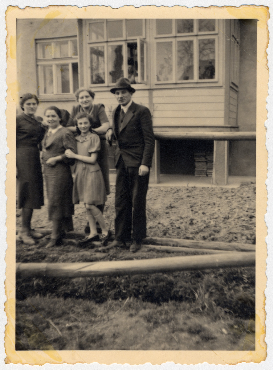 Group portrait of the Honig and Rozenblit families standing outside a building in Tarnow.