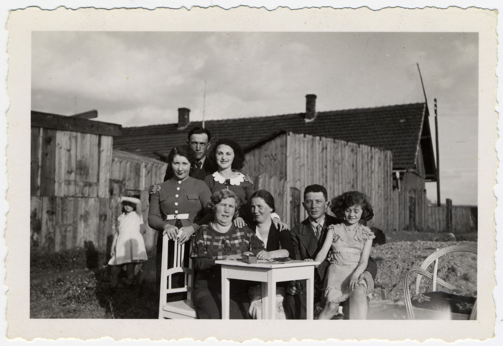 Group portrait of the Honig and Rozenblit family seated by a table outdoors.  Cesia Honig on right seated on father, Naftali Honig's lap. To the left of him sits mother Malka Honig. Alongside them stand various unidentified relatives.
