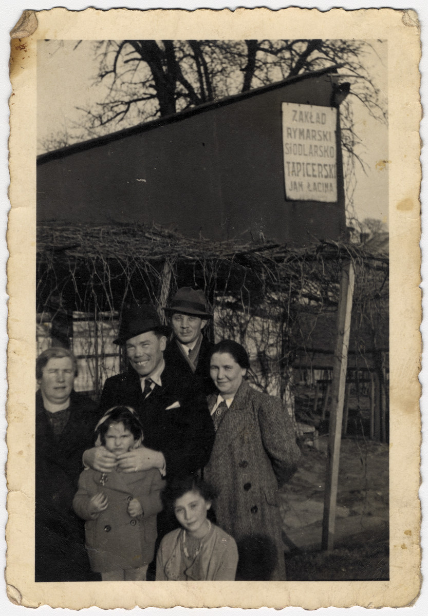 "A Jewish family from Tarnow poses in front of Jan Lacina factory.  Pictured are Cesia  Honig on very bottom pictured with her younger cousin Miriam to her left. Her maternal aunt and uncle Syma and Ziggy are on the left and her and mother Naftali and Malka Honig are on the right.  Cesia would later work in this same factory alongside her future Polish rescuers while in the Tarnow ghetto.       Text on back reads: ""April 1938"""