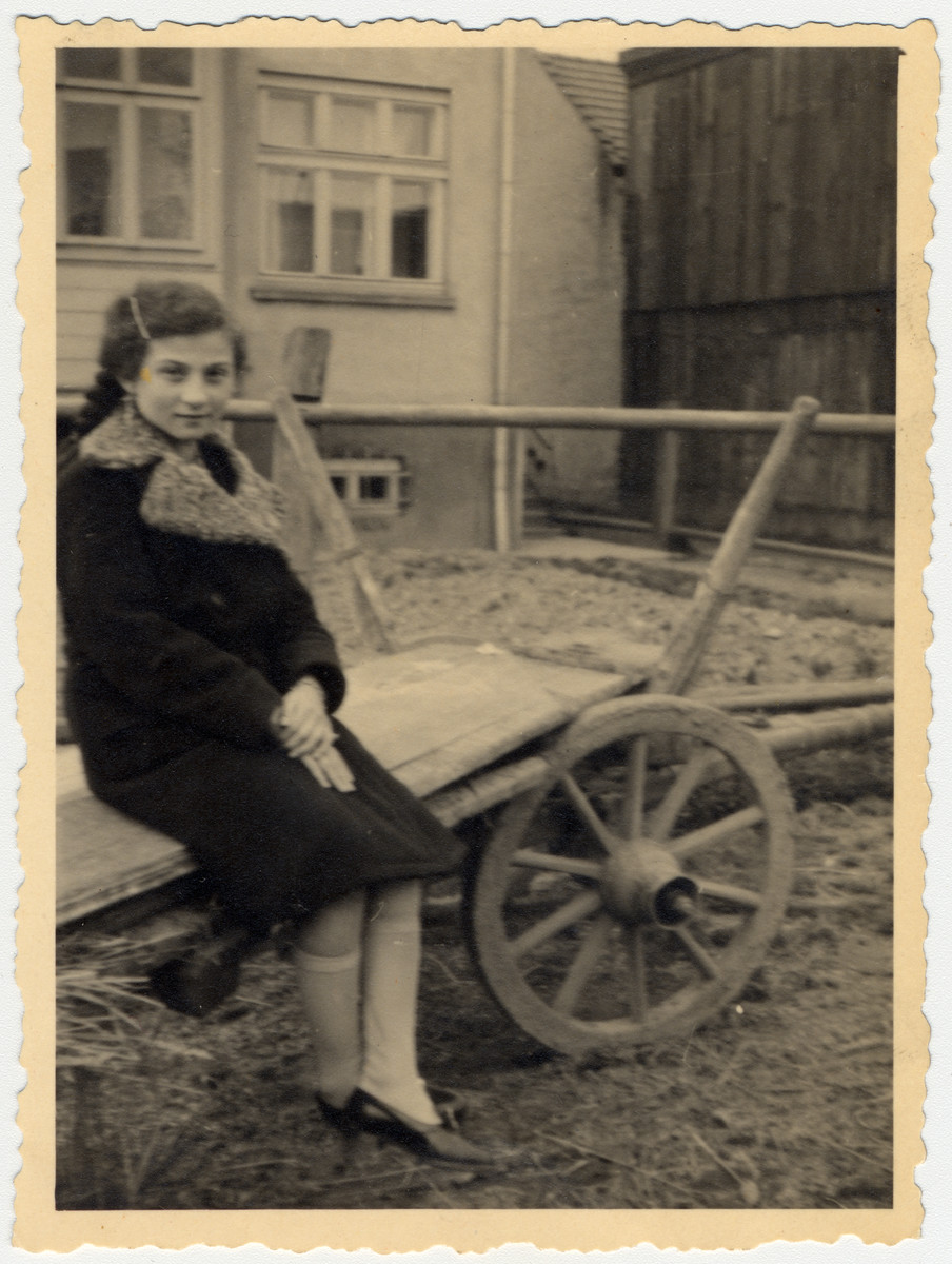 Cesia Honig sits on the side of a wagon.