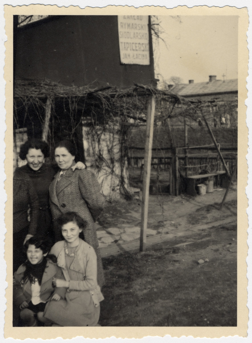 Cesia Honig in lower right pictured with mother, Malka Honig (upper right), aunt and cousin.  They are standing in front of Jan Lacina factory in Tarnow nearby where Cesia's aunt lived. The factory would later be the same one in which she worked alongside her future polish aid-givers in the Tarnow ghetto.