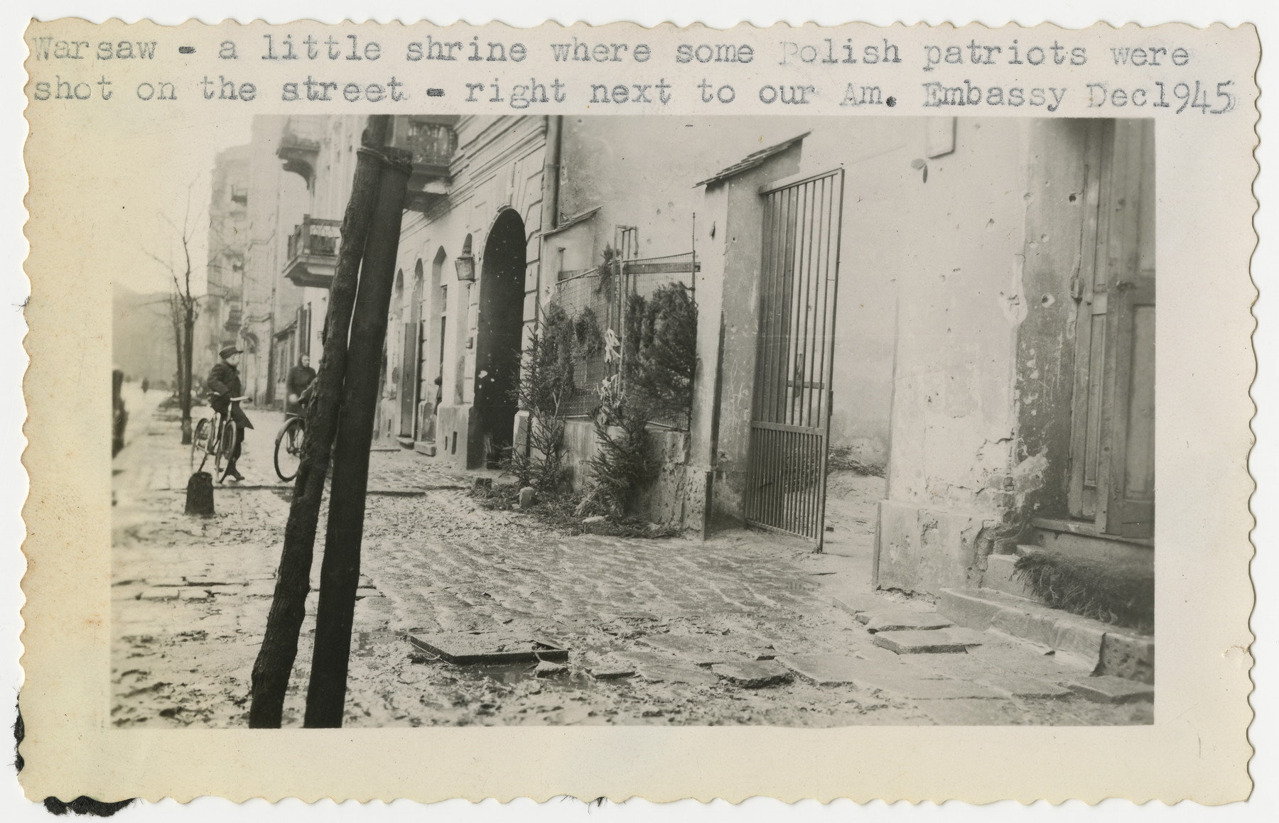 """Postwar street scene in Warsaw where wreaths hang by the site of the murder of Polish citizens.  The original caption reads """"A little shrine where some Polish patriots were shot on the street -- right  next to our American Embassy."""""""