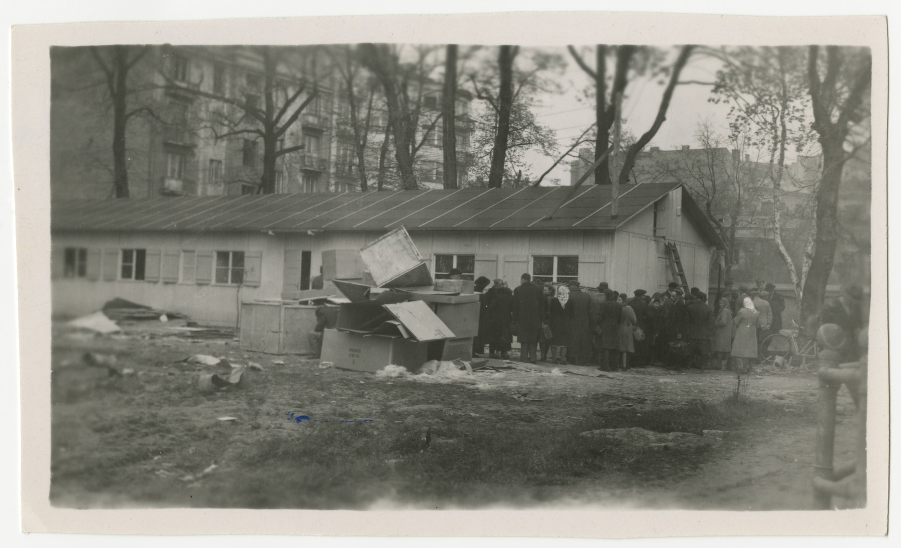 """Poles wait in line to apply for American visas.  The original caption reads: """"Waiting to get into the consular office to apply for visas to get to America.  Notice the makeshift building."""""""