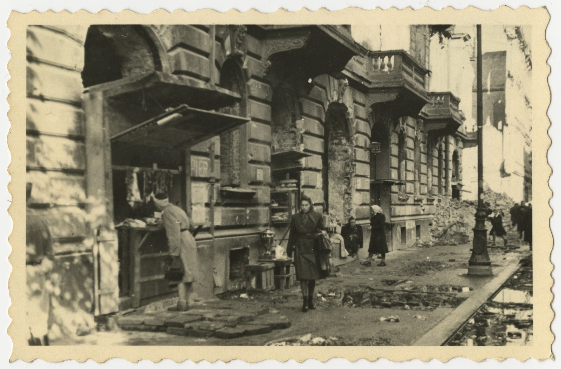 A Polish woman walks down a war-damaged the sidewalk while another looks at a store display in postwar Warsaw.