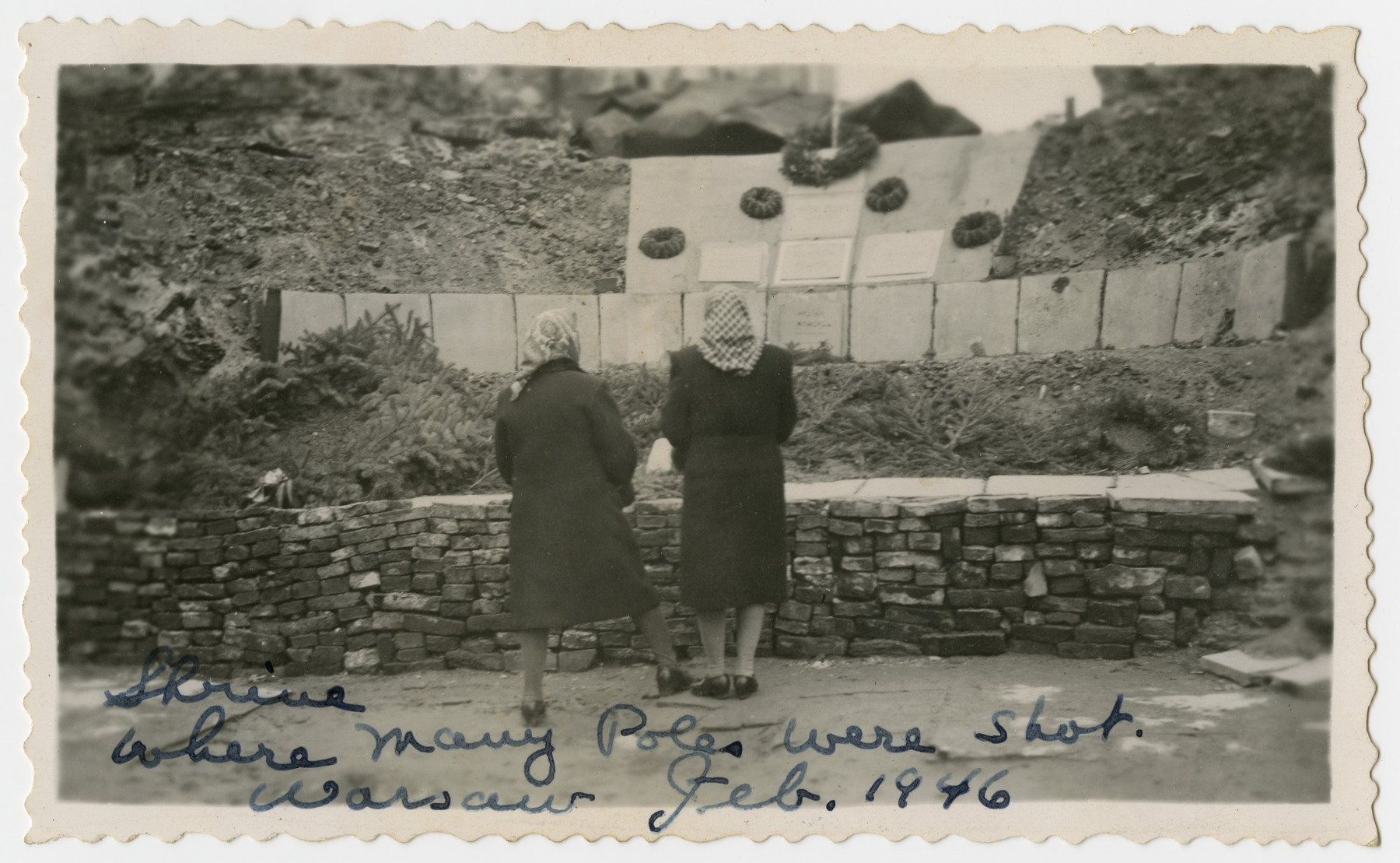 Two Polish women pay respects at a shrine where many Poles were shot.