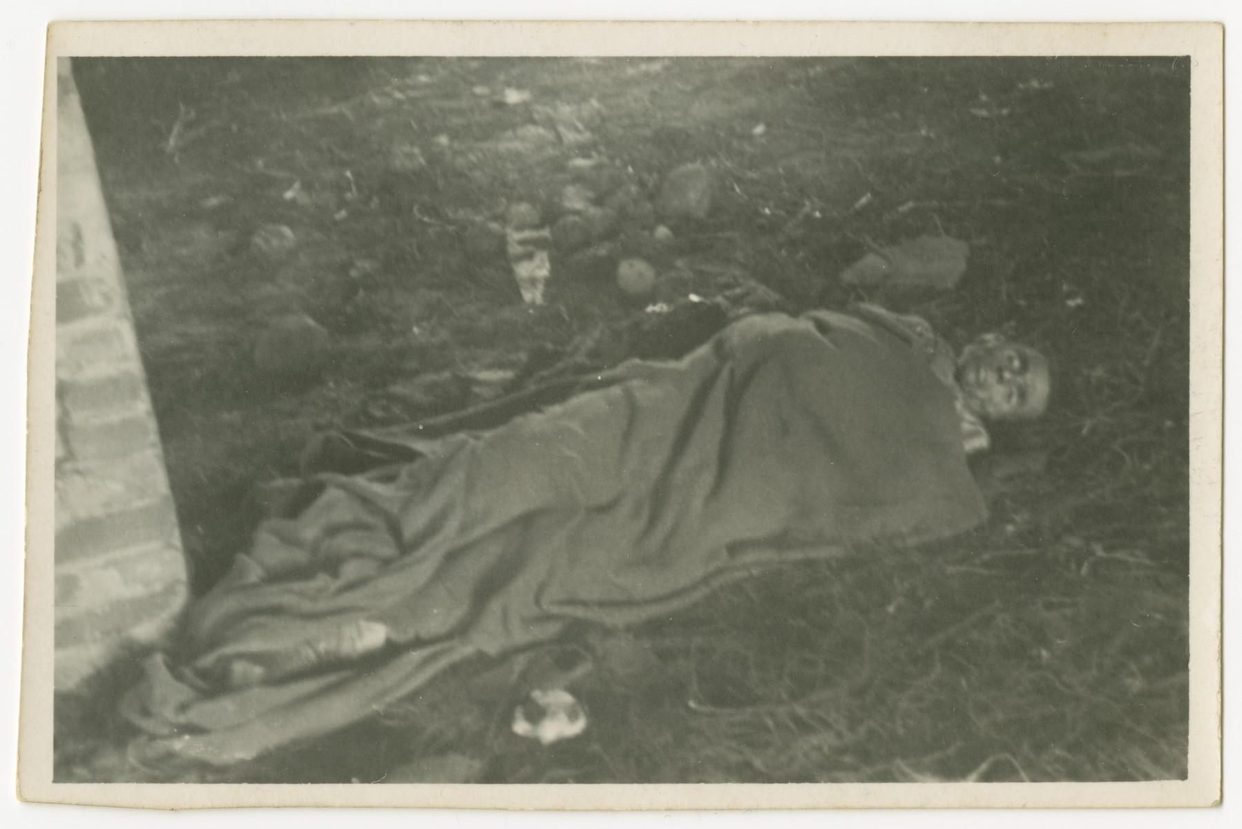 Close-up of a corpse covered with a blanket and lying on the grounds of the Woebbelin concentration camp.