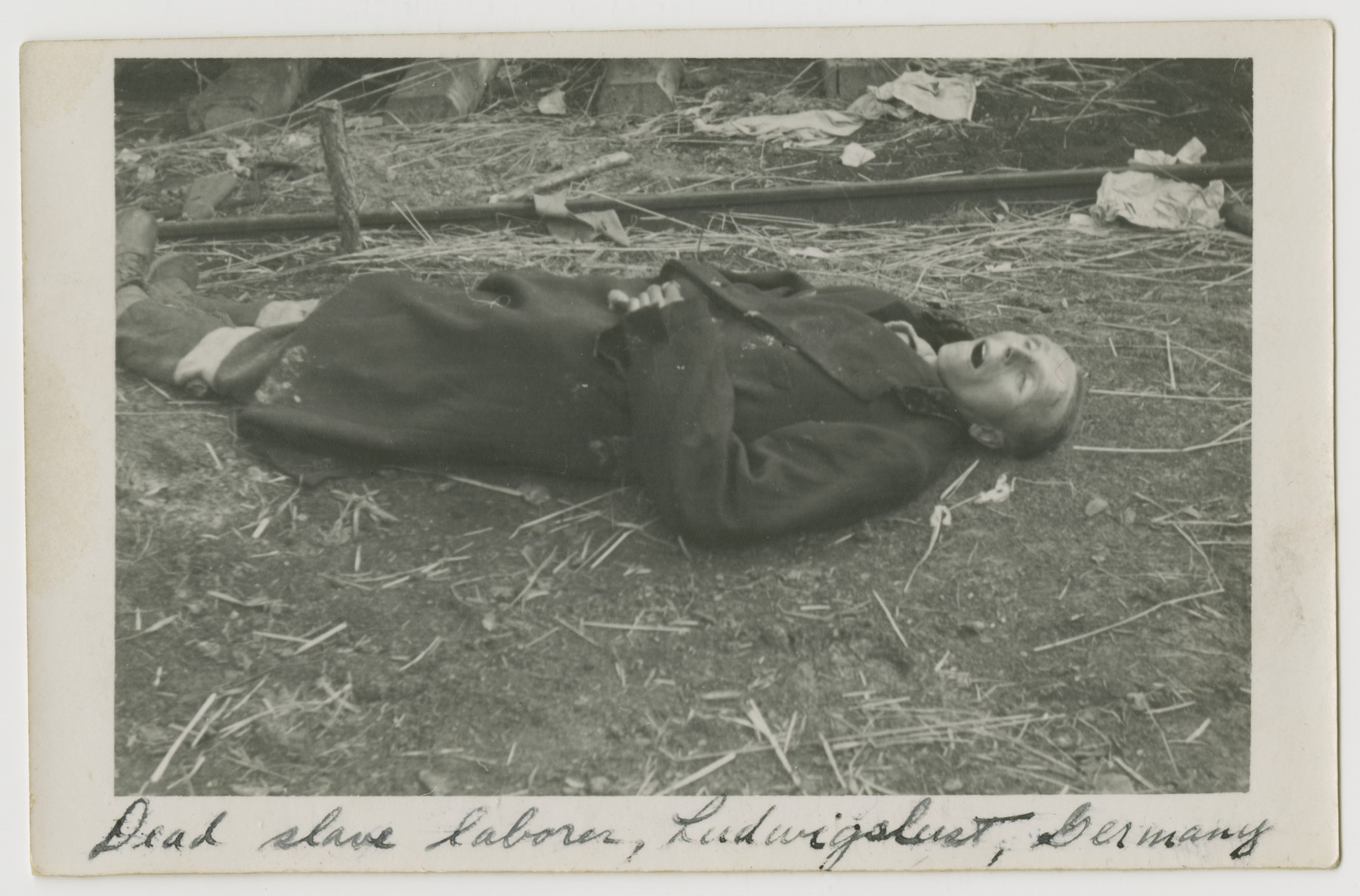 "Close-up of a corpse lying on the grounds of the Woebbelin concentration camp.  The photograph's original caption reads, ""Dead slave laborer, Ludwigslust, Germany"""