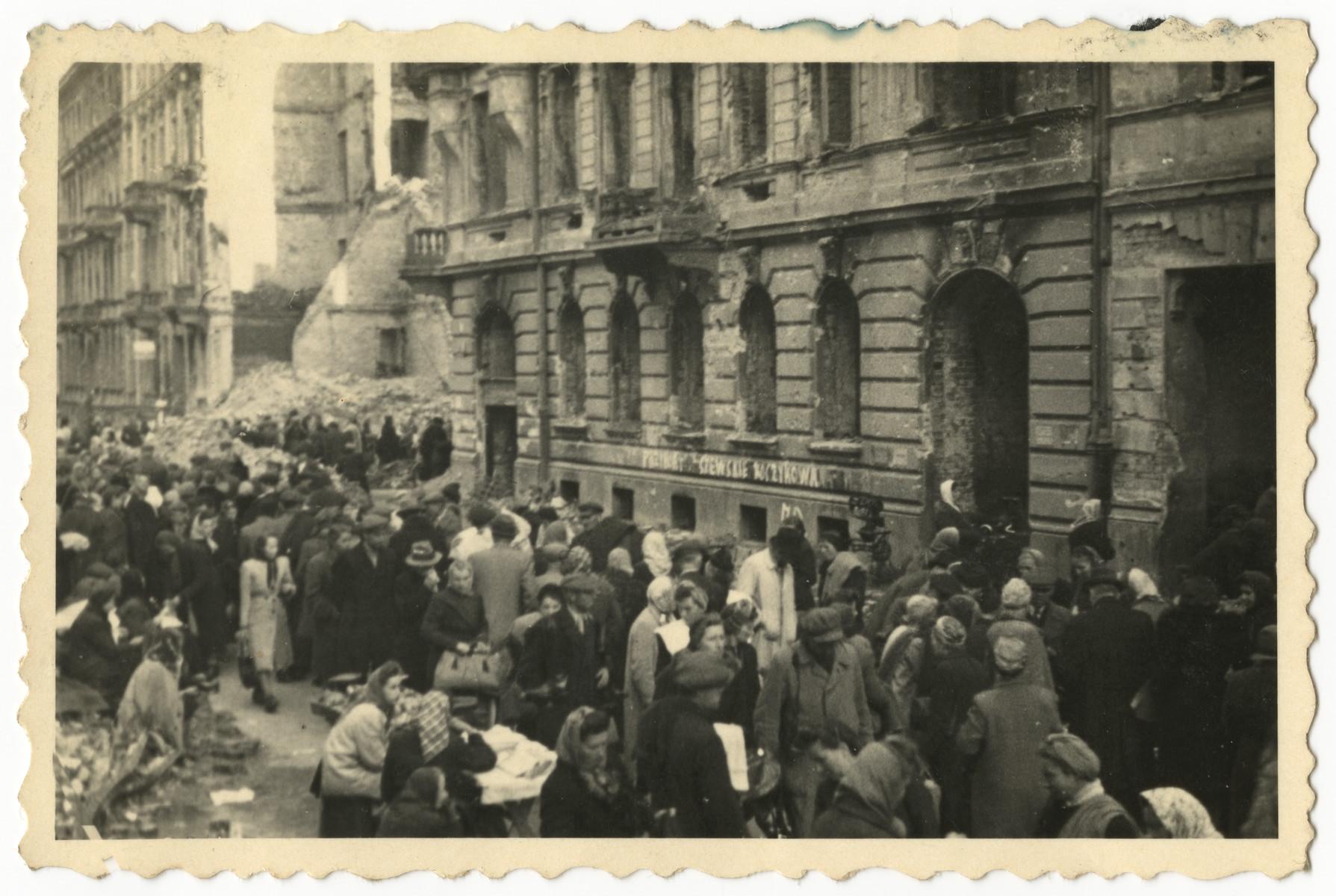 Polish men and women crowd into an outdoor market in postwar Warsaw.