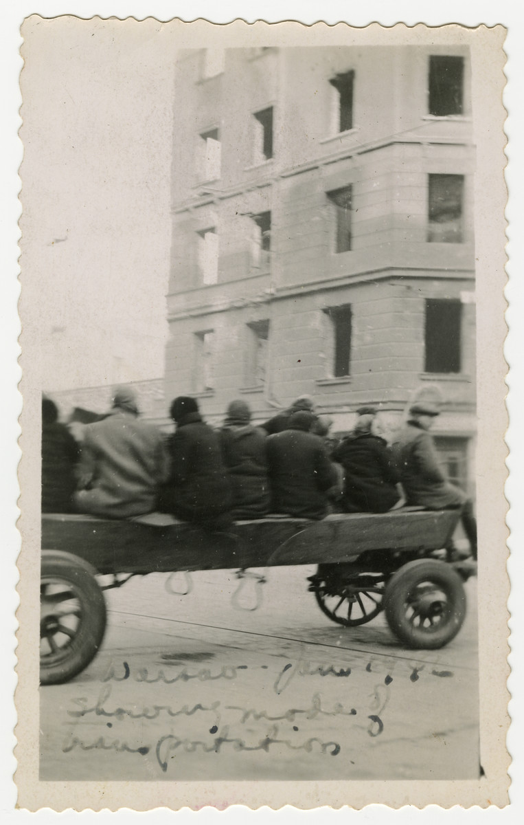 Polish women ride on an open cart through a street of Warsaw.