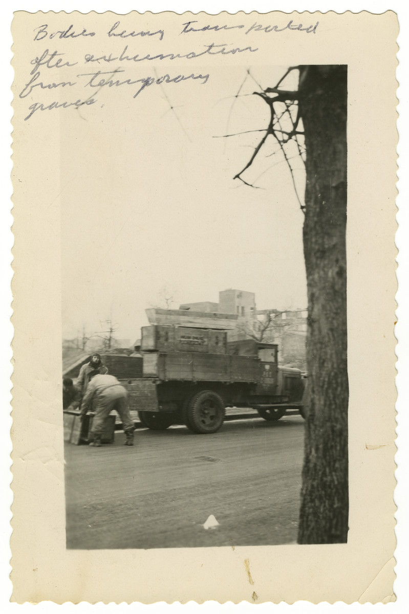 "Exhumed corpses are loaded in crates onto a truck.  The original caption reads: ""Bodies being transported after exhumation from temporary graves."""