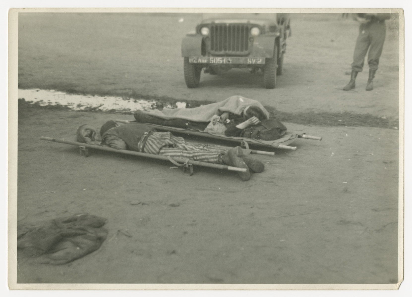 A soldier stands next  to [either two corpses or infirmed survivors] lying on stretchers.