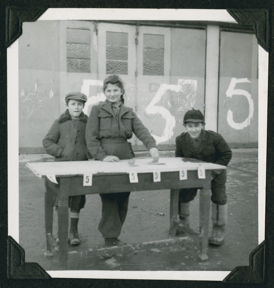 Three children stand by an election table for the World Zionist Organization at the Wetzlar displaced persons camp.