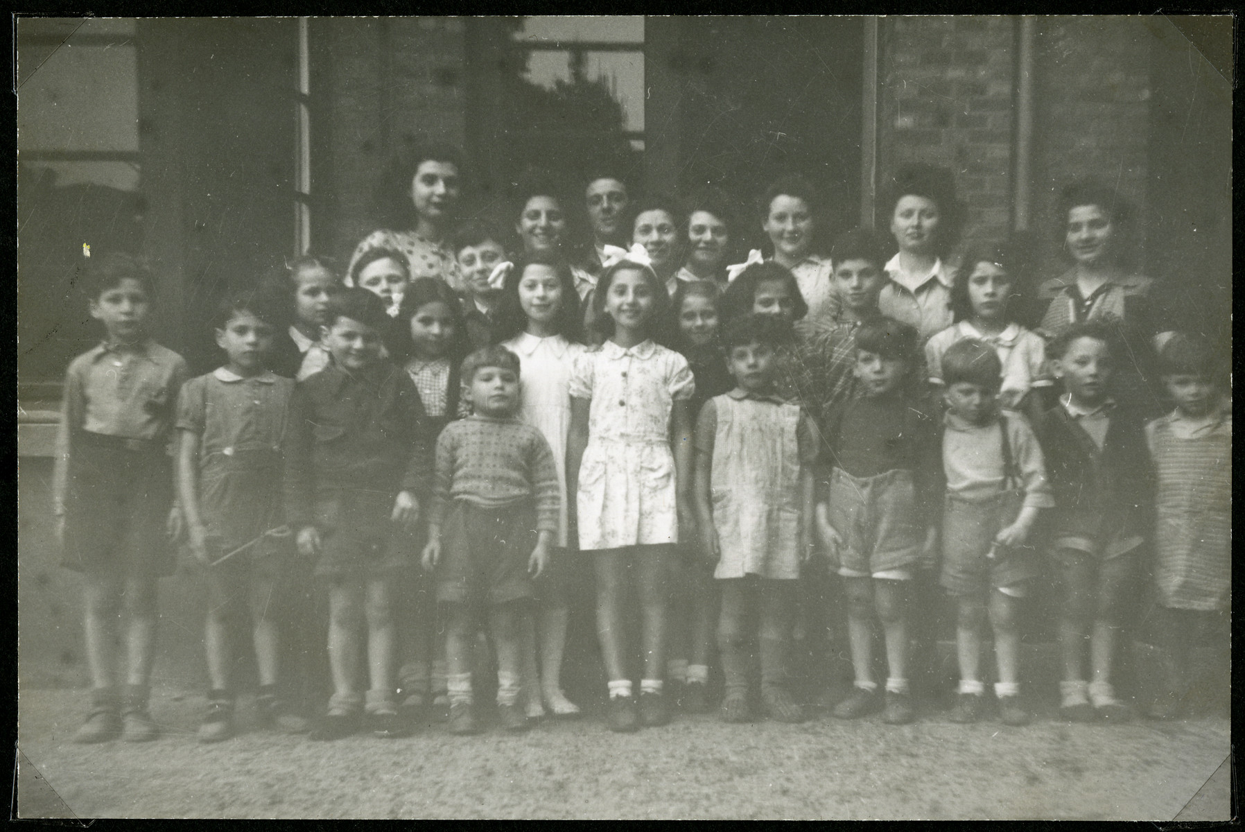 Group portrait of school children standing outside a building in an unidentified displaced persons camp.