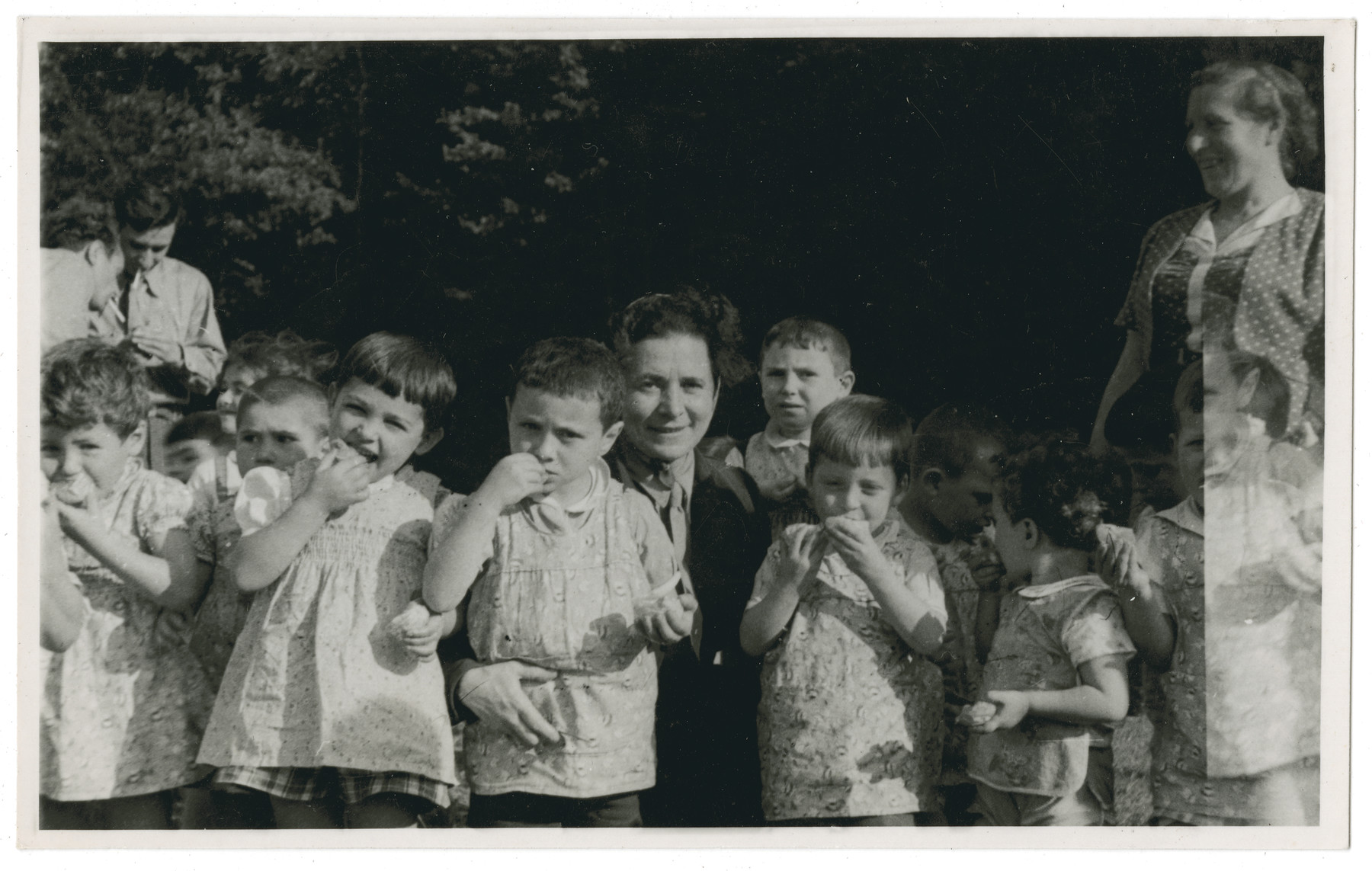 "Young children from the Lindenfels home enjoy an outdoor snack.  The original caption reads: ""Lindenfels school.  In the woods in the afternoon."""