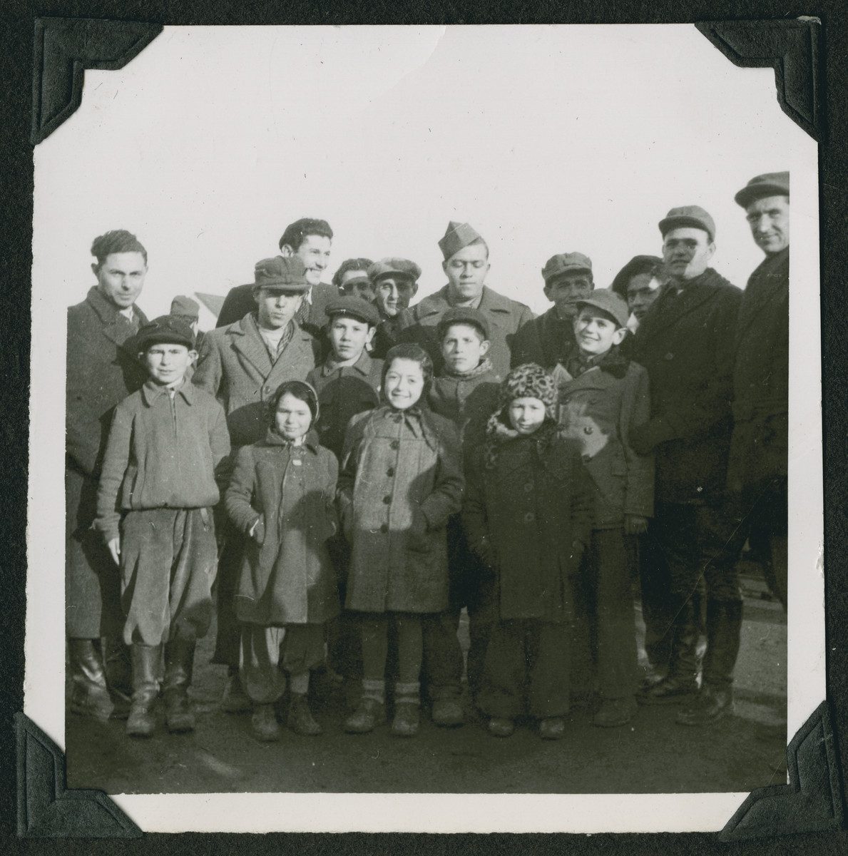 "A member of the Frankfurt Jewish GI Council poses with children and adults at the Wetzlar displaced persons camp.  The original caption reads: ""After the end of one of the quarters everyone swarmed out on the field to congratulate the players just like they do in the States after a quarter in a football game.  I took this opportunity to take a group picture."""