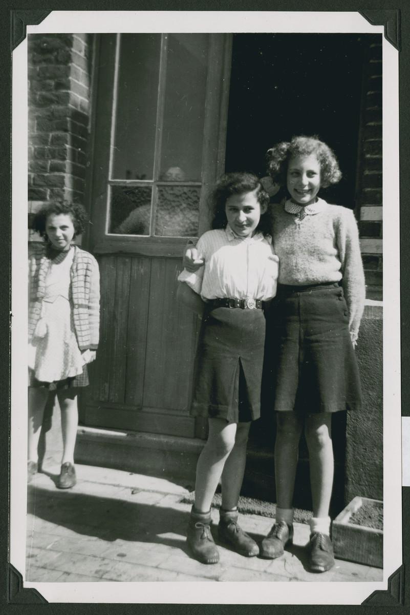 Close-up portrait of three girls in a hachshara in Marquain, Belgium.