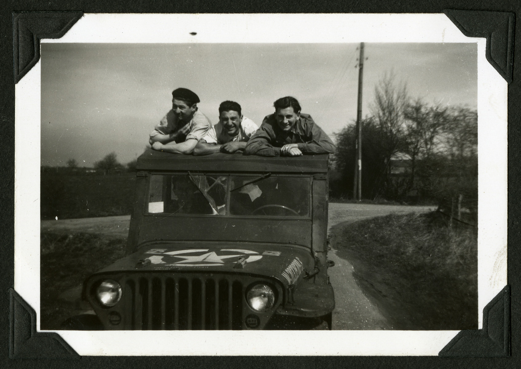 Three members of a hachshara in Leve, Belgium lean against the roof of a jeep.