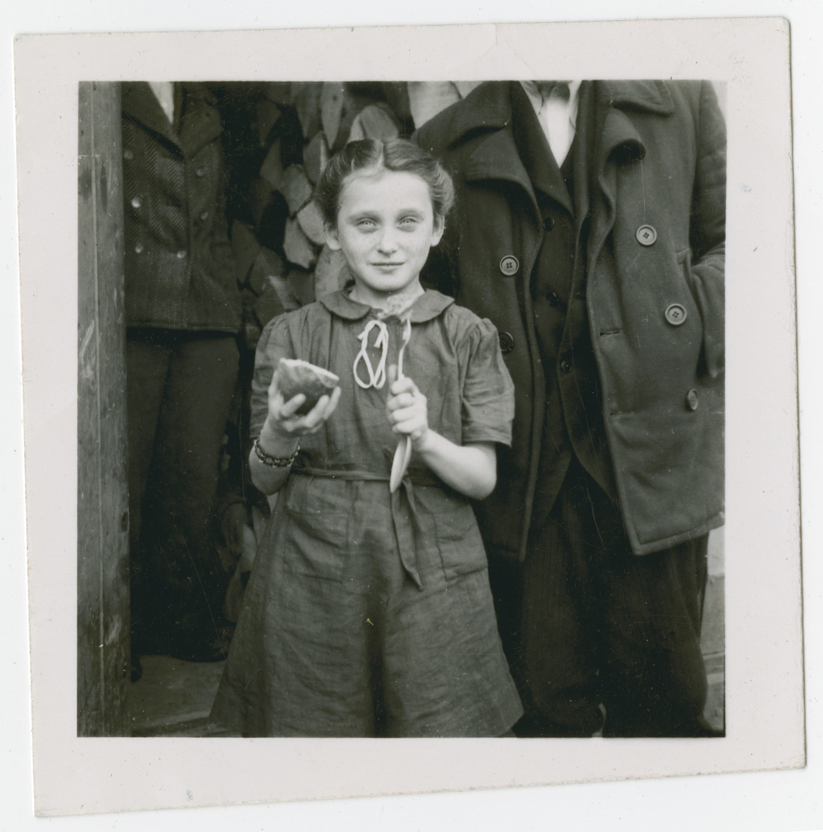 """A young girl in the Ziegenhain displaced persons camp shows off her dinner.  The original caption reads: """"Ziegenhain.  Little Jewish girl shows her dinner.  That is a 'piece' of meat at the end of her fork.  See it?"""""""