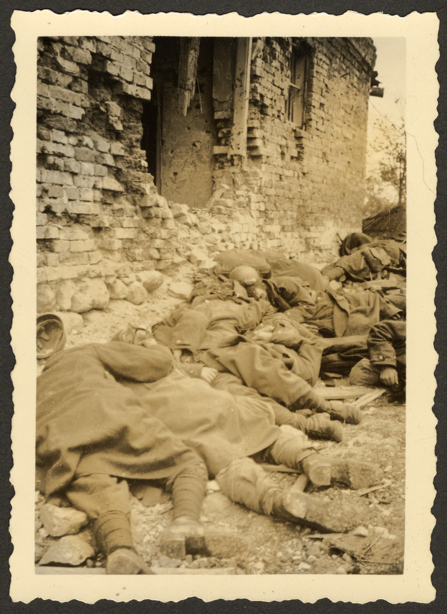"Fallen Polish soldiers in Zakroczym, killed during the invasion of Poland, lie on the side of a war damaged building.  Original German caption read: ""Polish soldiers killed in action in Zakroczym."""