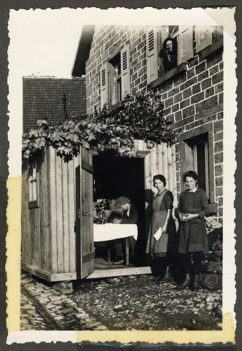 Two women from the Kalberman family stand outside their sukkah belonging to Emanuel and Rosa Kalbermann.  Standing on the left is Marta Rosenfeld Kalbermann.