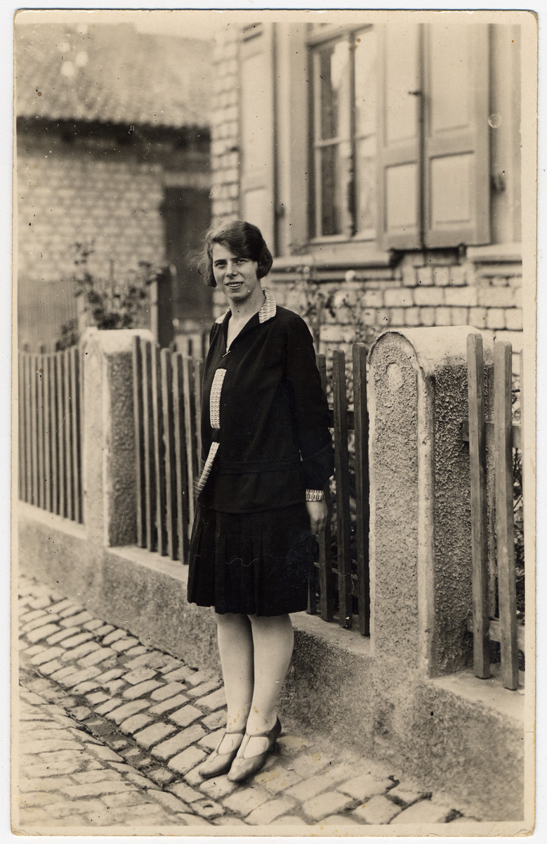 Portrait of Paula Kahn, a German-Jewish woman standing outside a building next to a fence.T  Paula Kahn, nee Kalberman, was born on July 15, 1908.  She and her husband Walter Kahn immigrated to Israel.