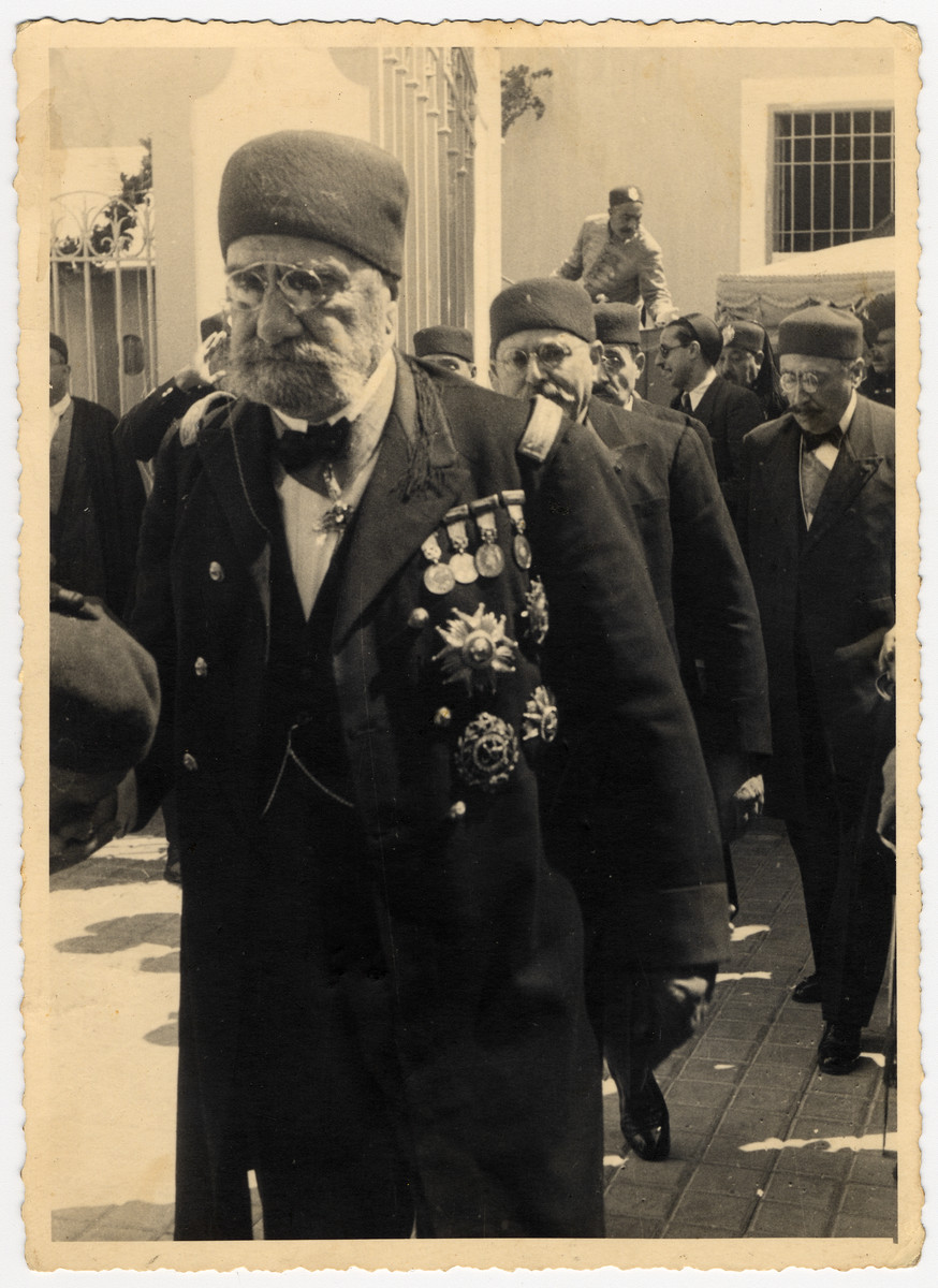 Ahmed Bey, the royal ruler of Tunisia, walks down the street.    Behind him is his prime minister Hedi Lakhoua and partially obscured is his Jewish physician, Dr. Emile Fellous.