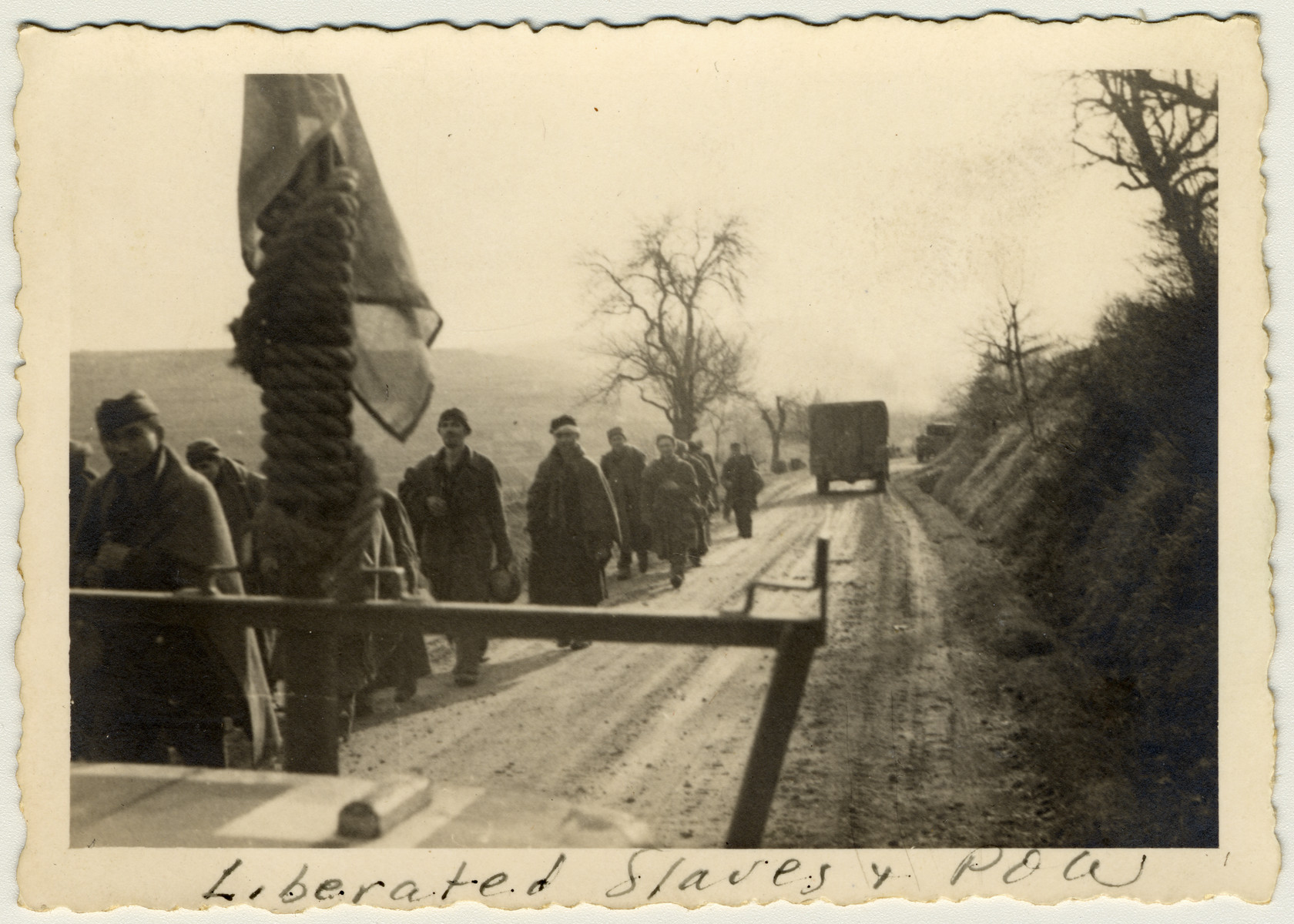 """Camp survivors and freed POWs march down a road after their liberation.  The original caption reads: """"Liberated slaves and POW."""""""