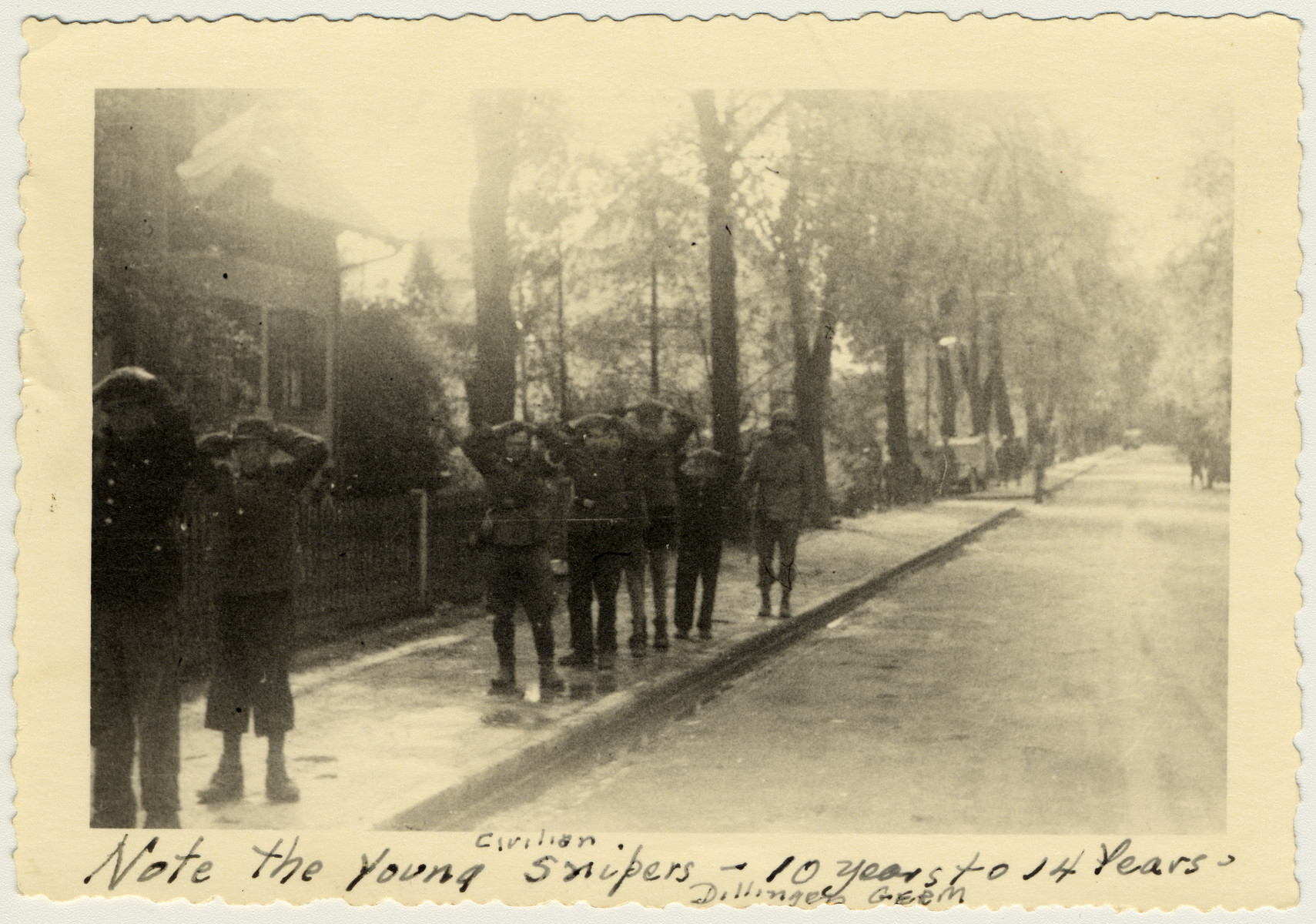 "Captured Germans stand in a line with their hands on their heads.    The original caption reads ""Note the young civilian snipers -- 10 years to 14 years""."