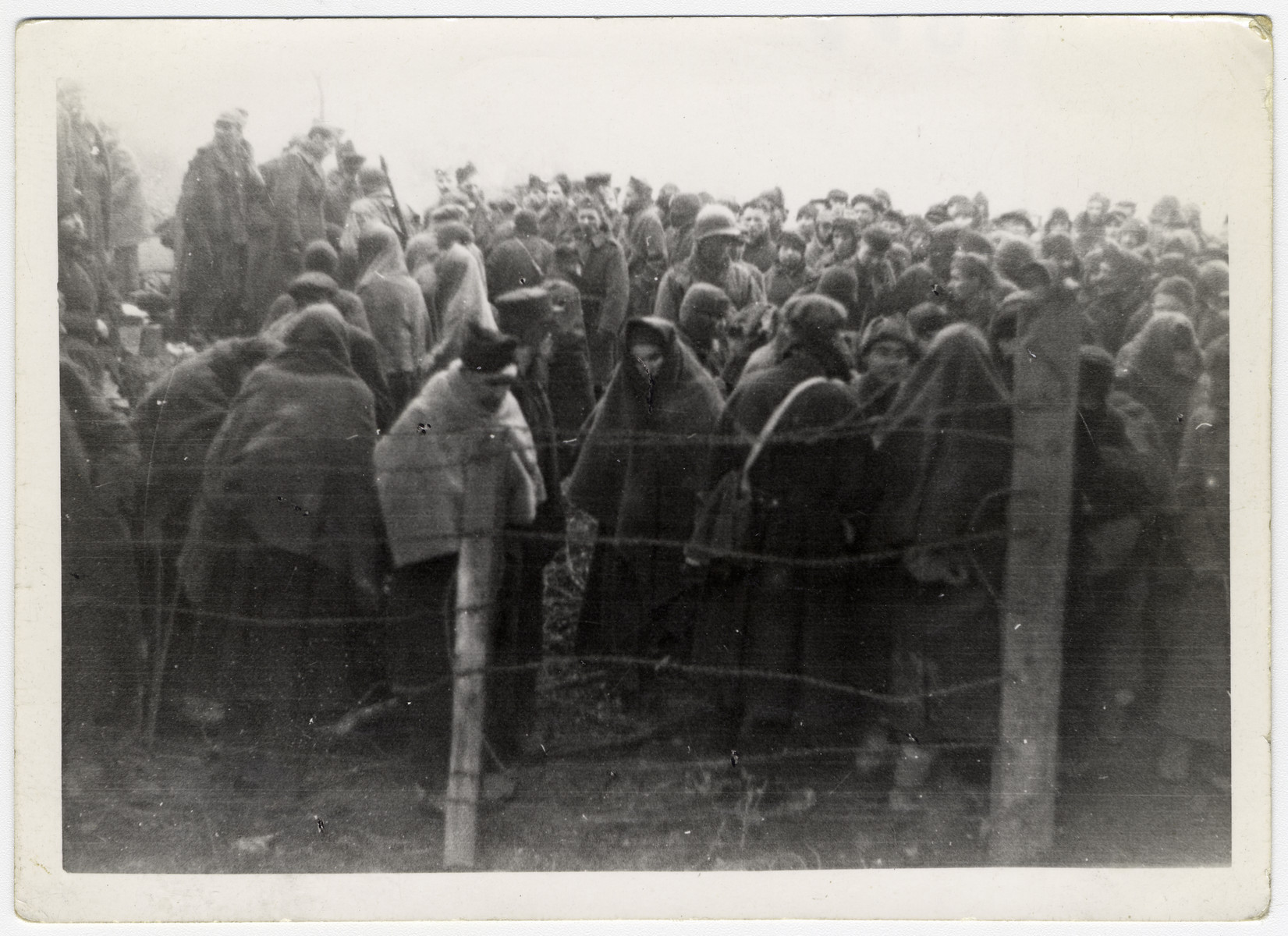 Survivors wearing blankets for warmth crowd together behind a barbed wire fence shortly after liberation.