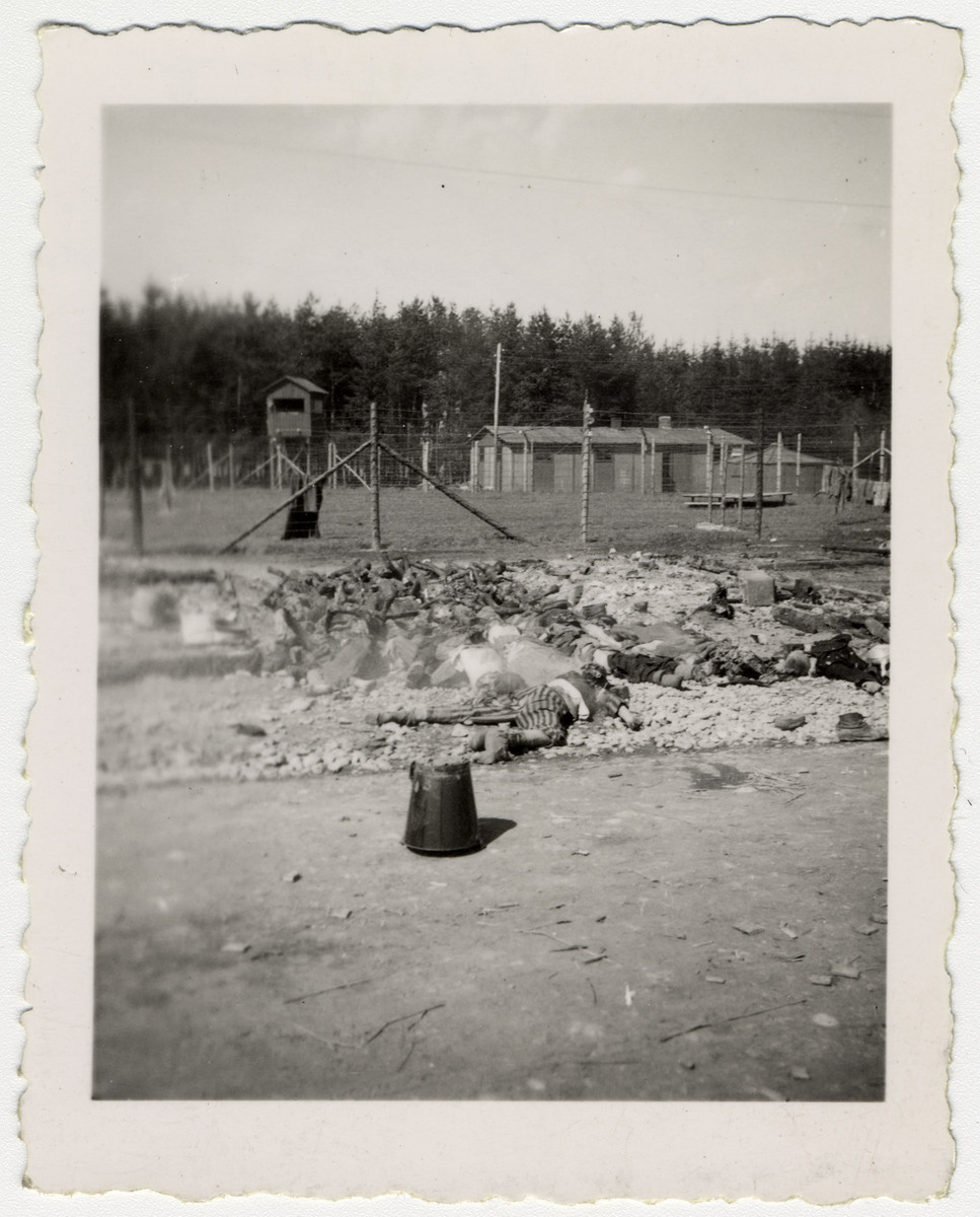 "Bodies and bones of dead prisoners lie piled near the fence of the Landsberg concentration camp.  The original caption reads: ""Dead burning Jews of concentration camp in Landsberg, Germany""."