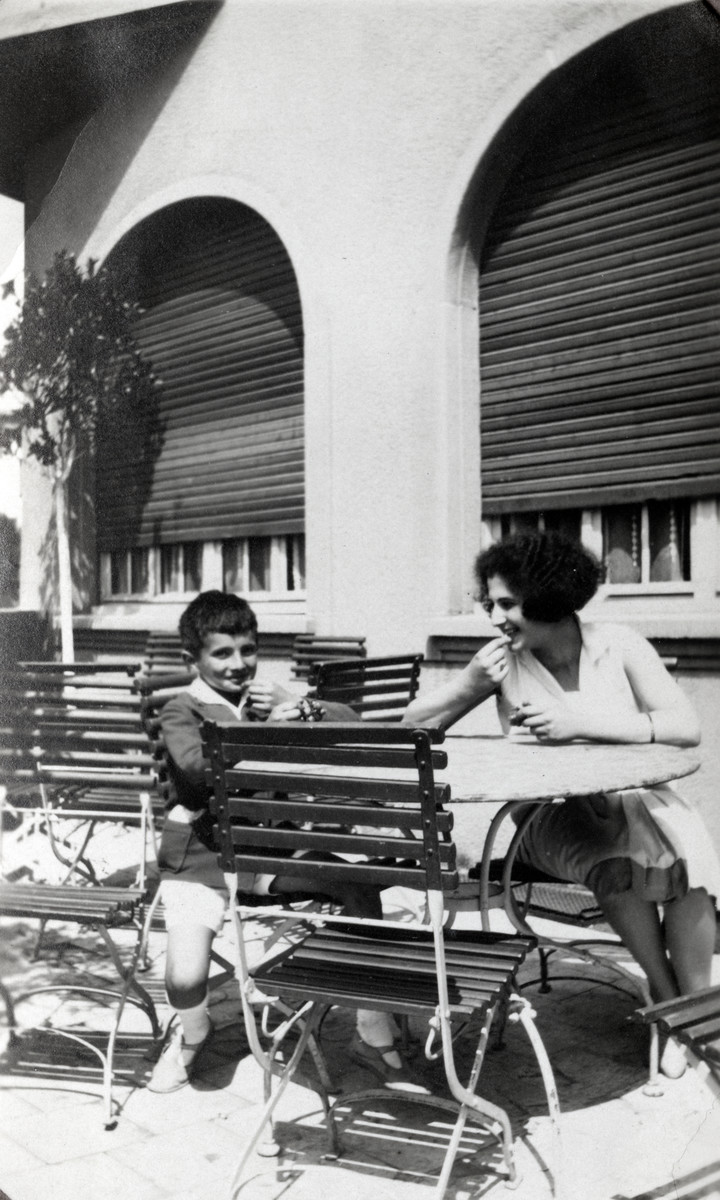 Germaine and Andre Levy sit outdoors at a table.