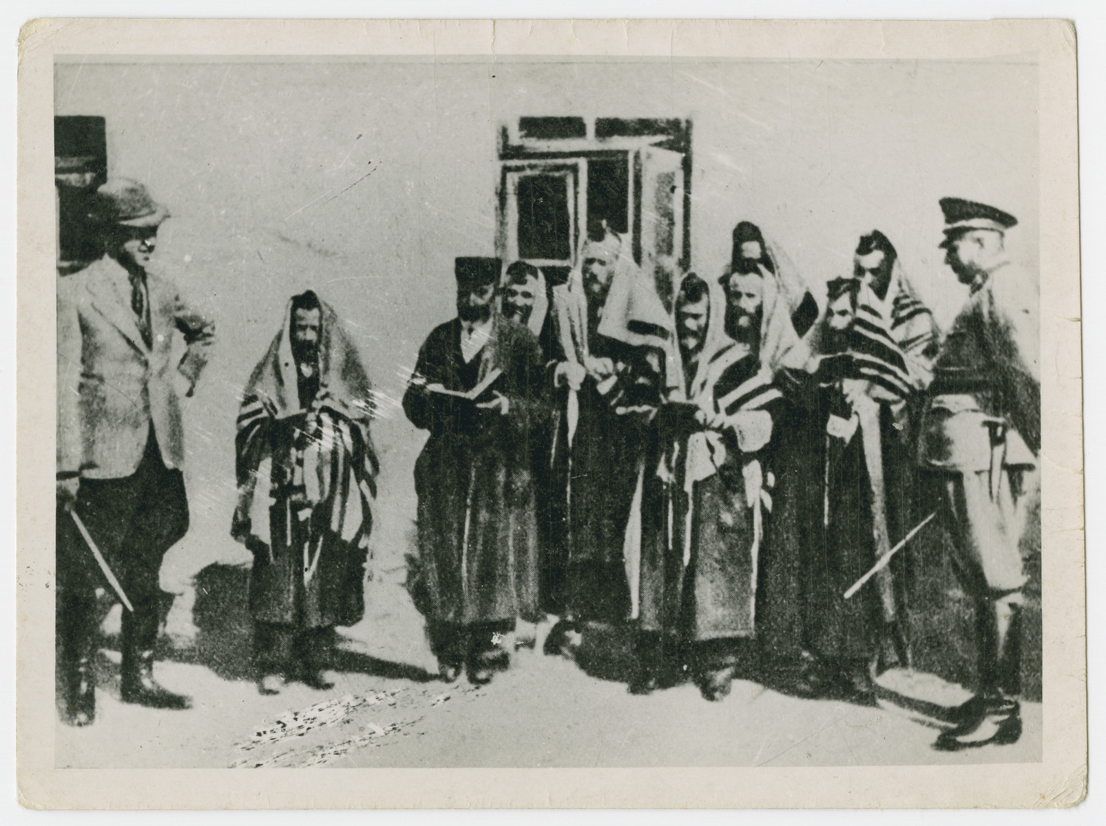 A Nazi soldier and civilian publically humiliate religious Jews by forcing them to pray outside in an unidentified ghetto.