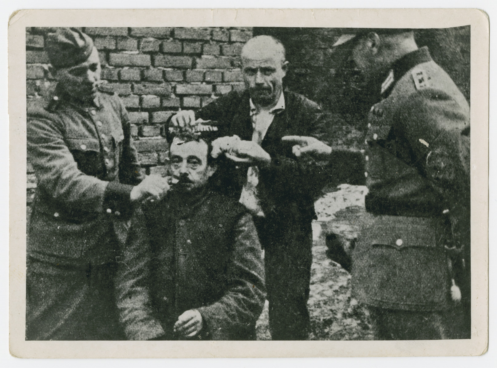 German soldiers force a man to shave the beard and hair of another [probably a religious Jew] in an act of public humiliation.
