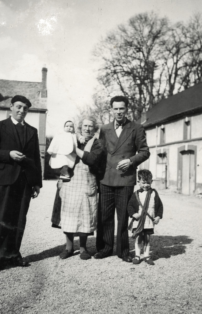 The Michel family poses on a street in Epernay prior to fleeing to the Free Zone.  Pictured left to right are Uncle Constant, Grandmother holding baby Marc, Marcel, and Jacques.