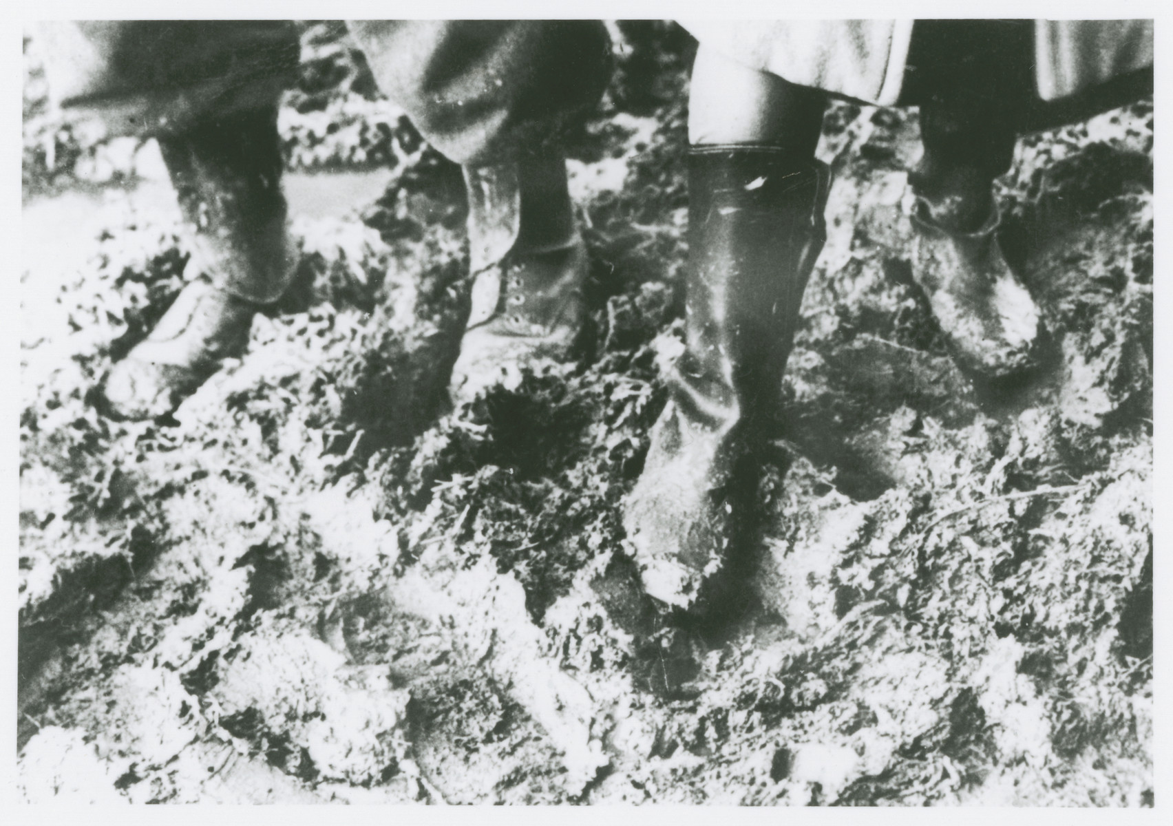 Close-up of the feet of two prisoners walking through the mud at the Novaky labor camp.
