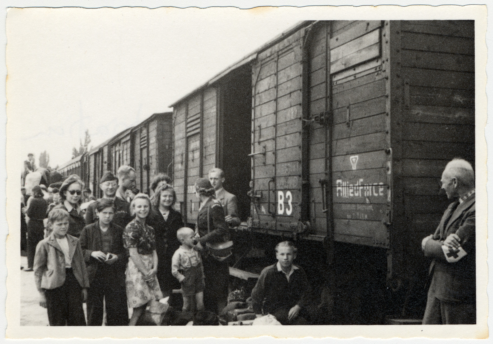 UNRRA director Mordecai Schwartz accompanies displaced persons awaiting repatriation to a waiting train.
