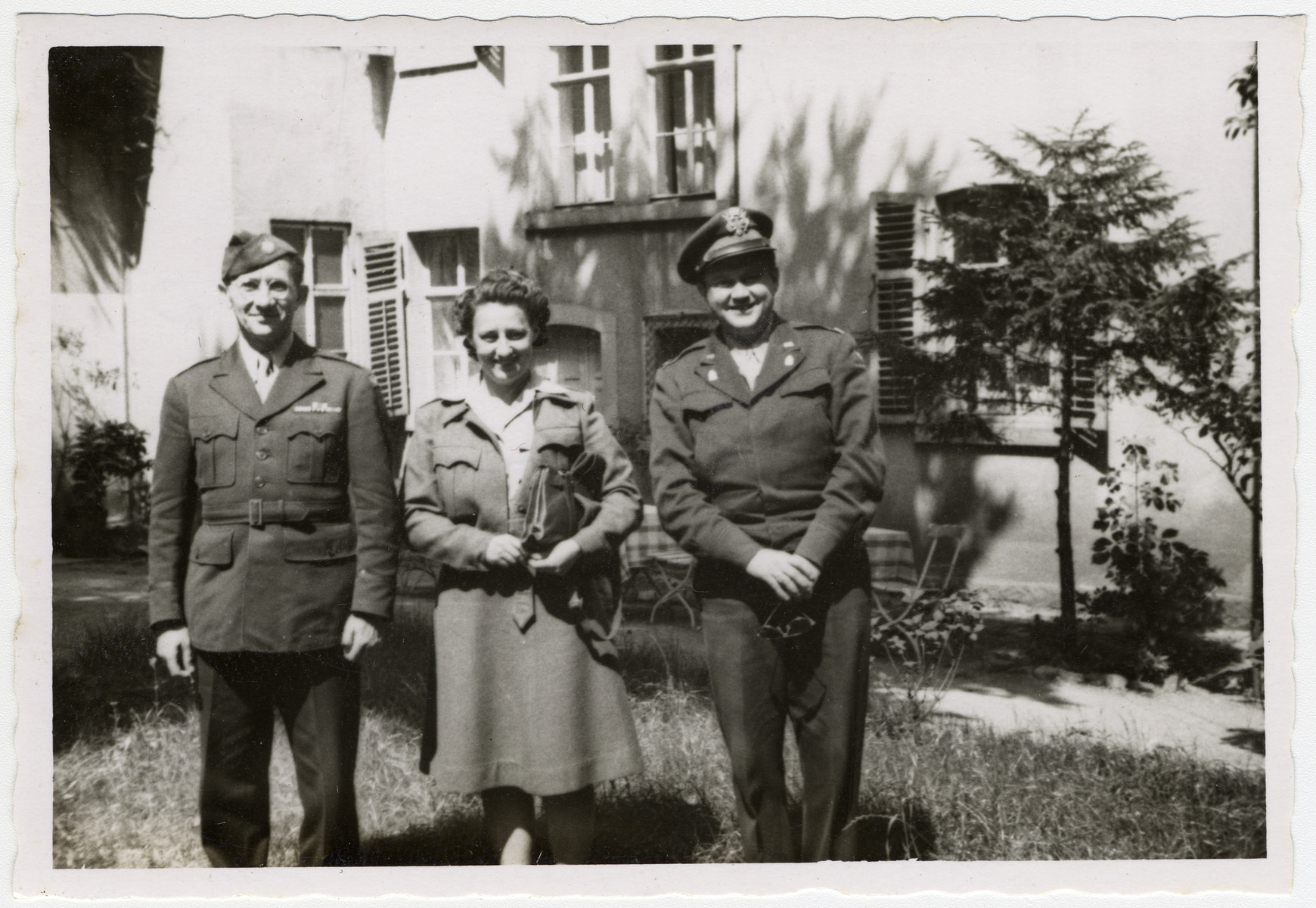 """Portrait of three UNRRA staff members.  Mordecai Schwartz is on the left.  The original caption reads: """"Military Mission to Camp"""""""
