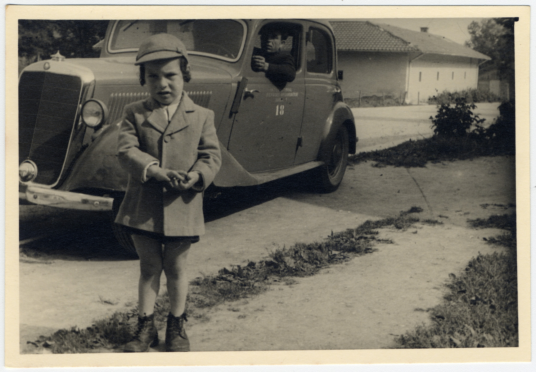A young chassidic child stands in front of an automobile in an unidentified displaced persons camp.