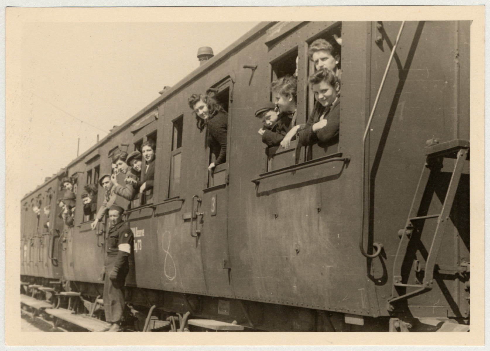 Displaced persons look out the windows of a train as they prepare to return home and be repatriated.