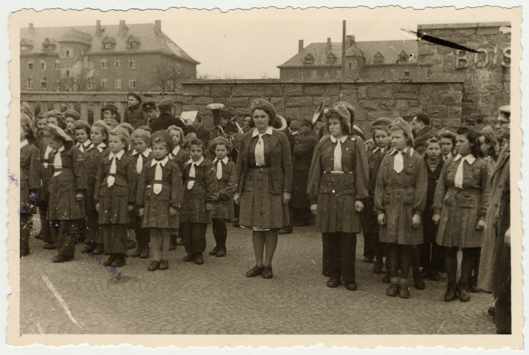 Children in uniform stand at attention in the Aschaffenburg displaced persons' camp while a band plays in the background.