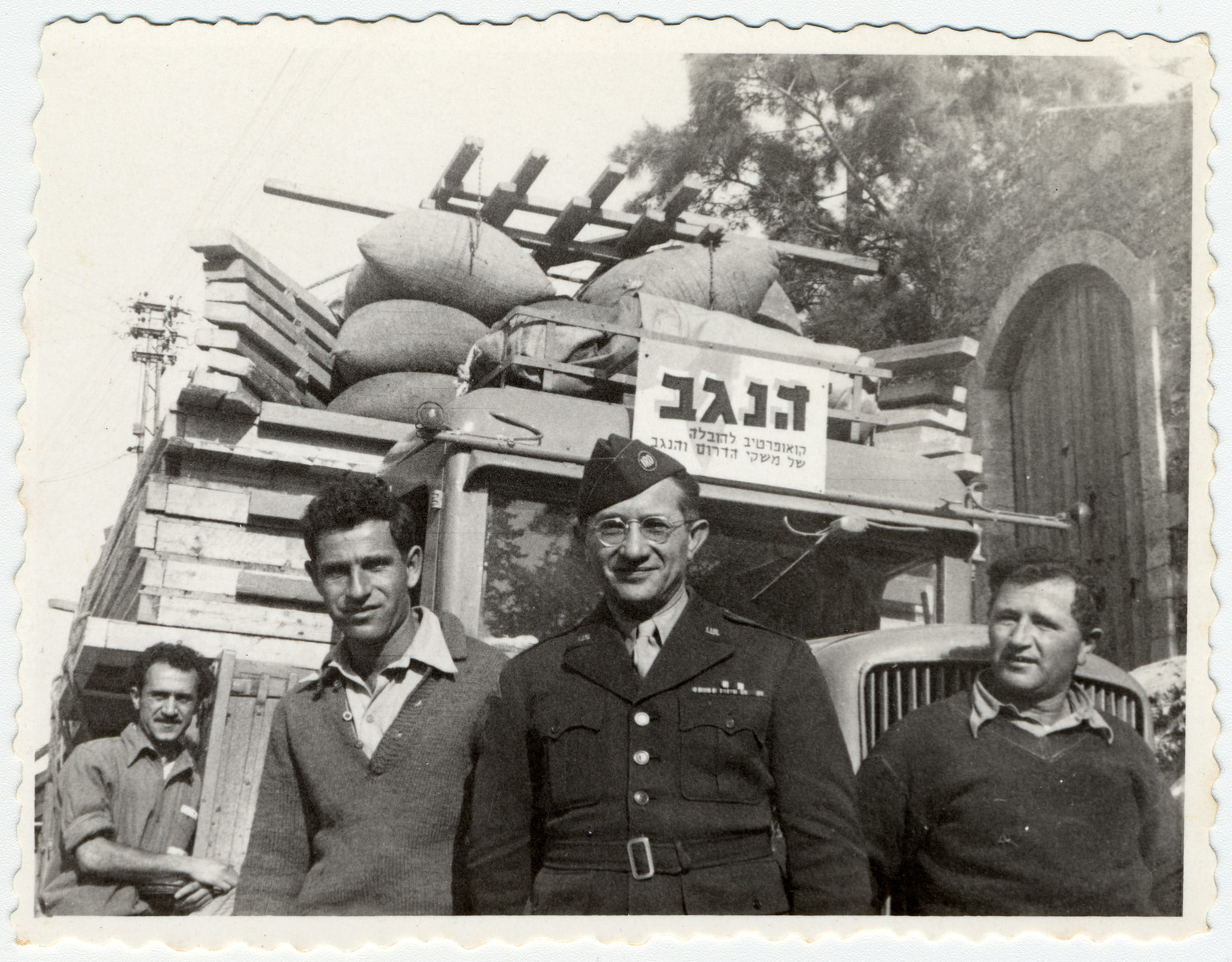 UNNRA director Mordecai Schwartz poses in front of a truck loaded with bundles and lumber to resettle Jewish displaced persons in southern Israel.