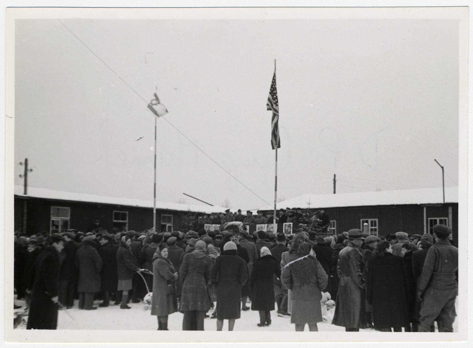 Jewish displaced persons in Munich attend a rally in the snow in an open courtyard with both American and Israeli flags flying.