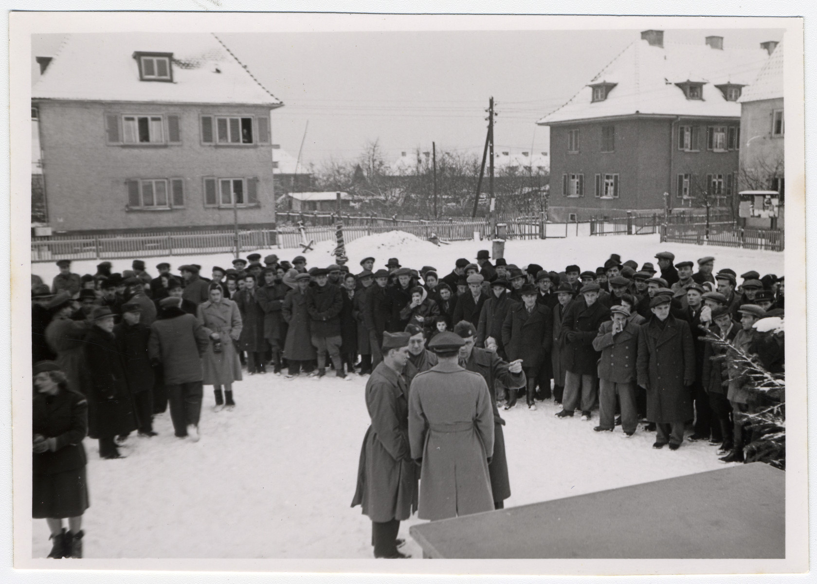 Jewish displaced persons' stand outside in an open snowy courtyard while UNRRA officials hold a discussion in the foreground.