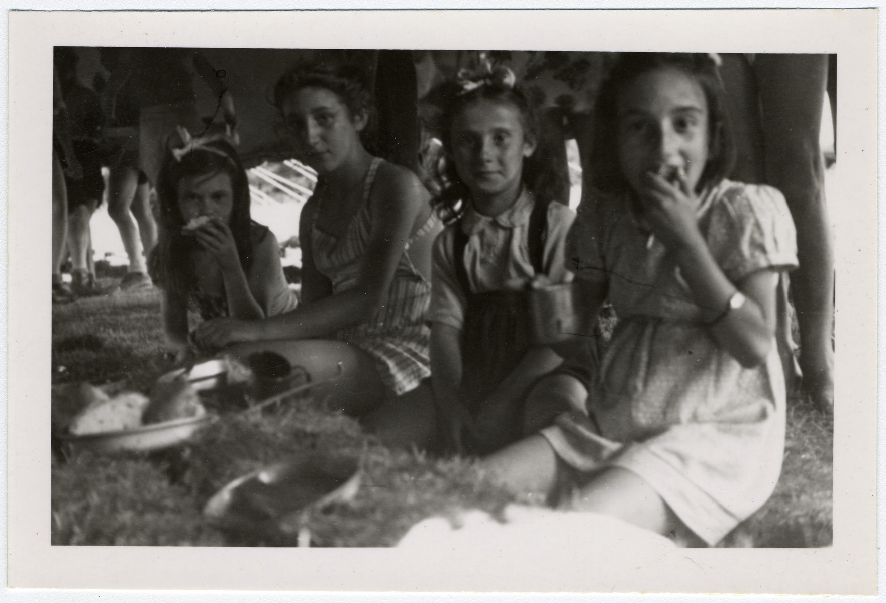 Four girls sit on the ground in a tent eating a meal in an unidentified displaced person's camp.