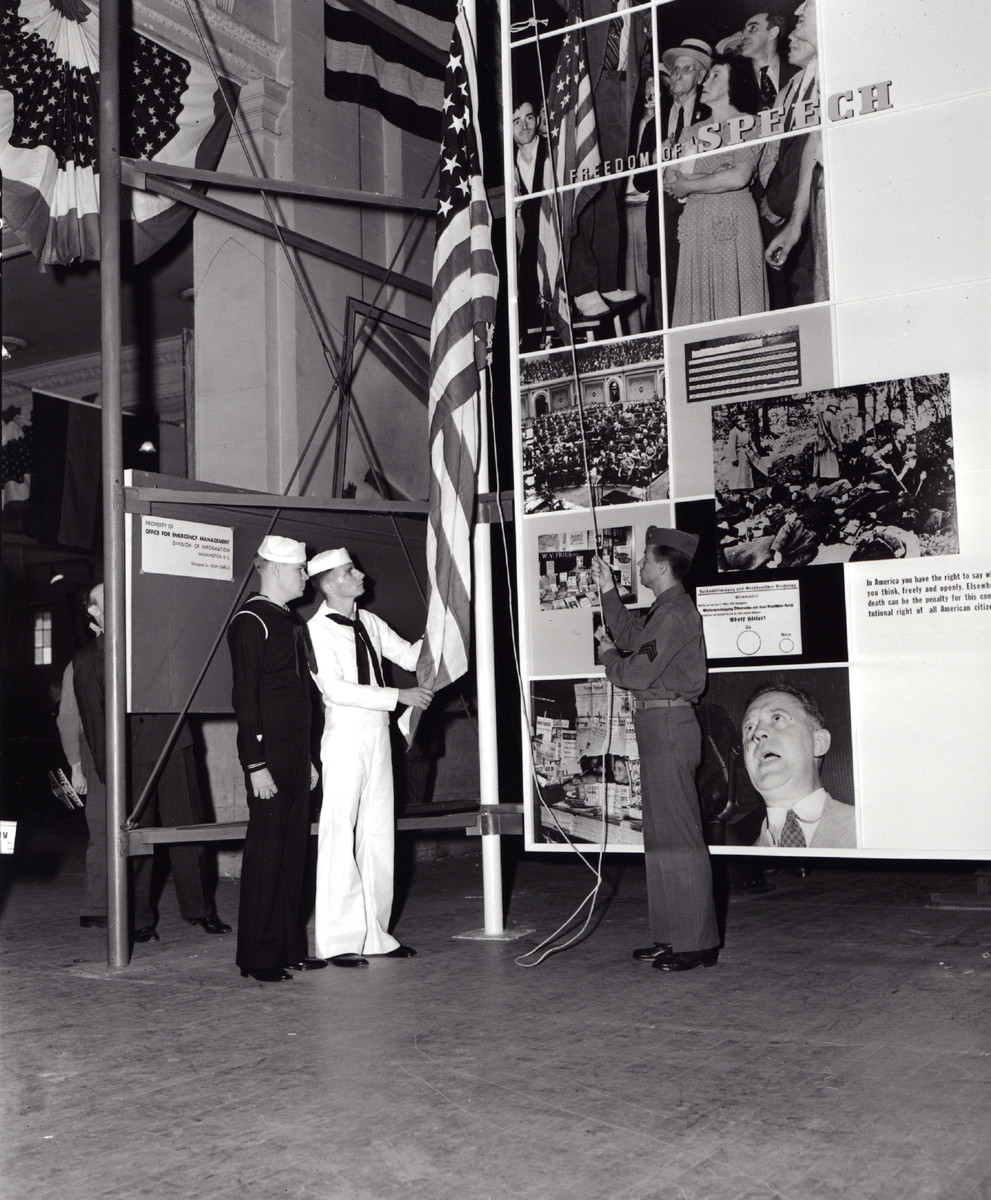 """Description reads: """"Old Glory being raised before a Four Freedoms photomontage.""""   In his state of the Union address, Roosevelt enunciates the Four Freedoms: freedom of speech and expression, freedom of worship, freedom from want, and freedom from fear."""