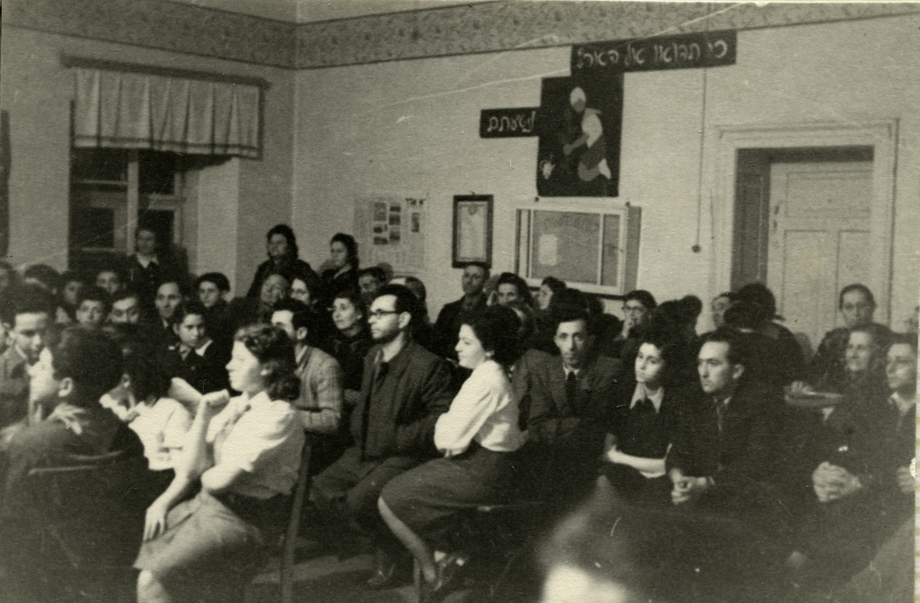 "Jewish youth gather for a meeting with a member of the Haganna in the Kloster Indersdorf children's home.  The sign on the wall reads ""when you come to the Land."""
