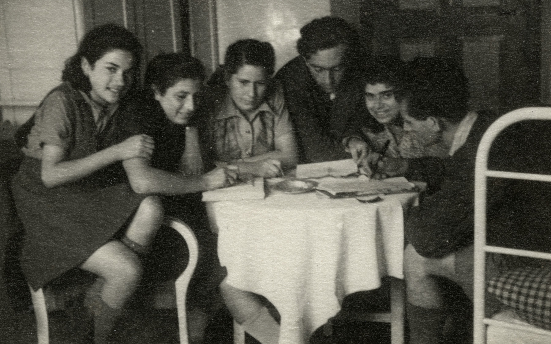 Members of the Kloster Indersdorf cultural committee meet around a table.   From left to right are Henia Bugajewicz, Masha, Hela Gelberg, (unidentified), Genya Riba and unidentified.