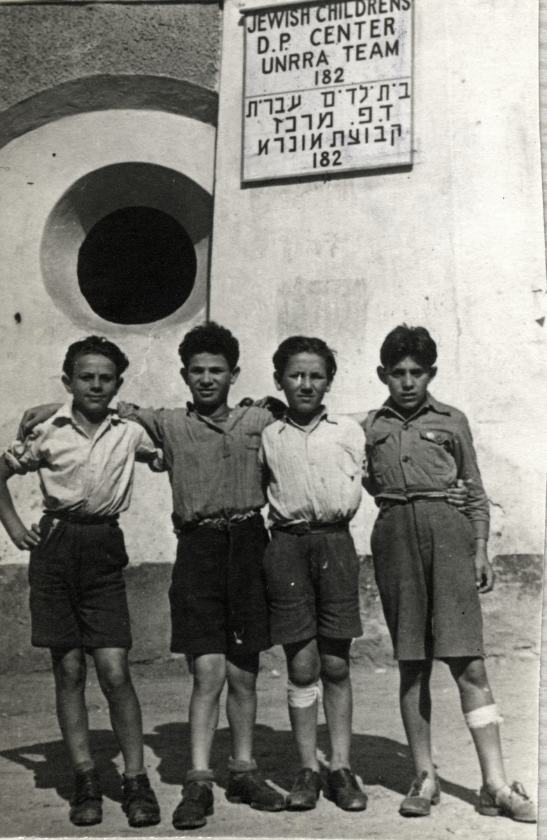 Four boys pose together in front of a Hebrew/English sign at the Kloster Indersdorf children's home.