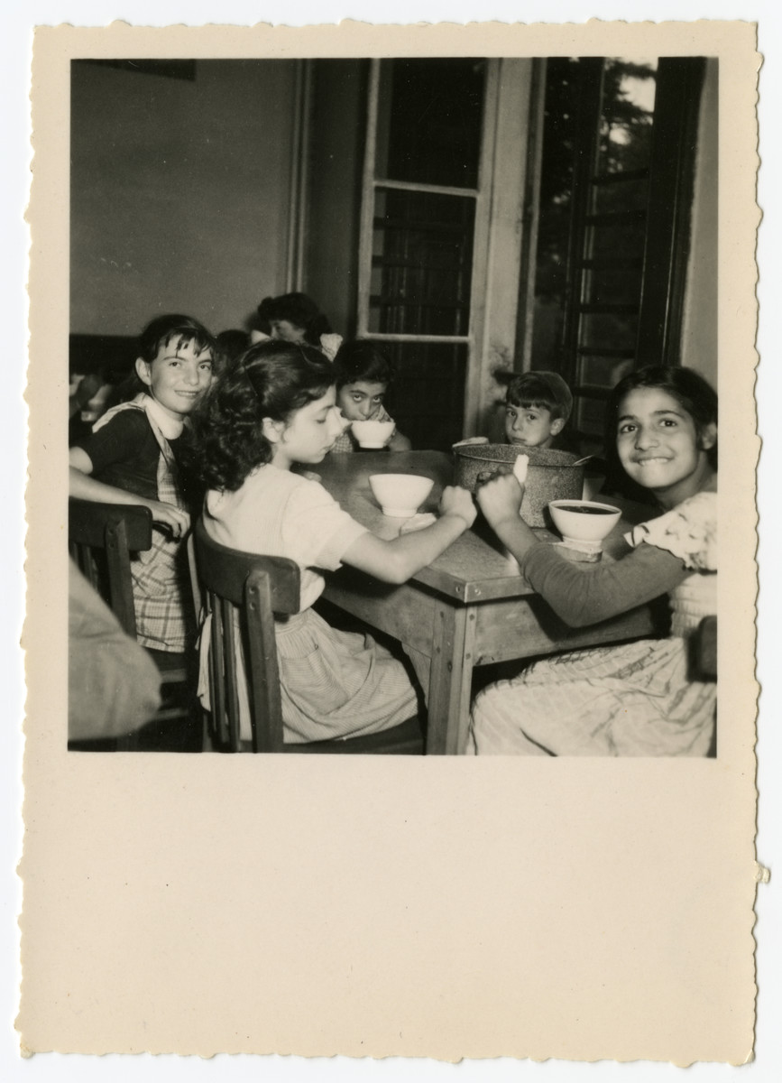 Children eat a meal in the  OSE Taverny children's home.  Beate Zimmern is facing the camera on the left behind Francine.  Edmee is sipping her soup to the left of my sister. The counselor Helene Ekayser Weksler is seated in the back, partially obscured.
