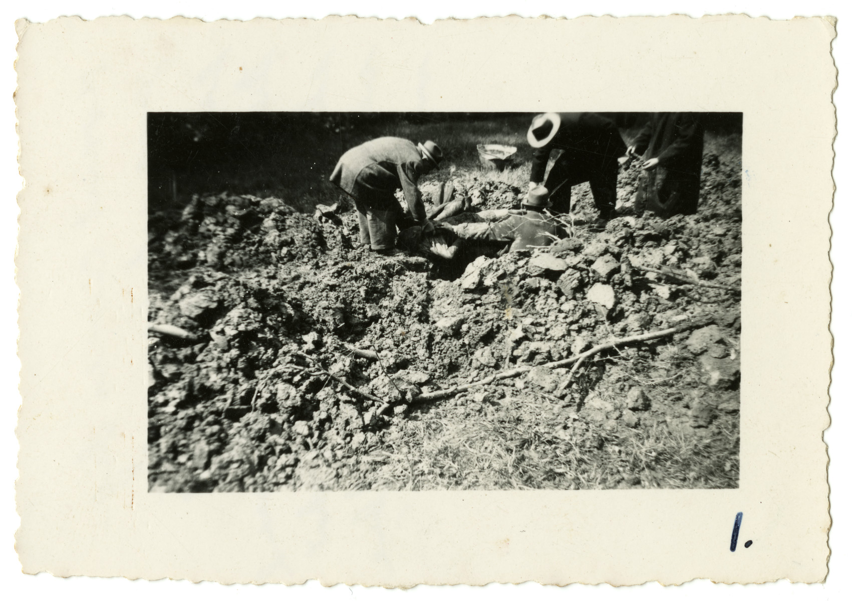 "Germans are forced to rebury the corpses of slave laborers who were killed near Essen shortly before the end of the war.  Original caption reads:  ""Kraut civies digging up for reburial part of the several thousand slave laborers that were murdered near Essen, Germany, May 45."""